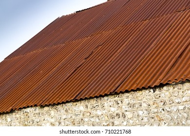 Agricultural barn with flint walls and red rusting corrugated steel roof