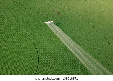 An agricultural crop duster flying low, and spraying a potato field