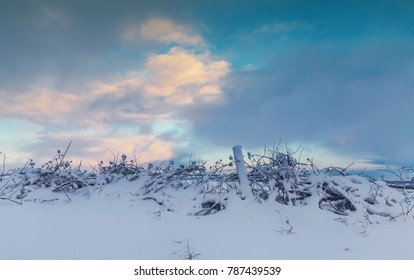Agricultural fence covered in snow at sunset. Shropshire Hills in United Kingdom