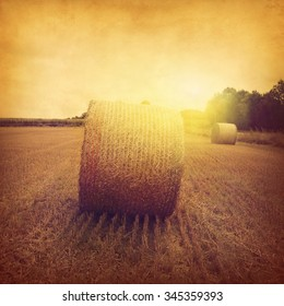 Agricultural field with hay bales at sunset in grunge and retro style.