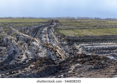 Agricultural field on which drove heavy vehicles. Ruts from the wheels in the mud, formed after the rain. Photo closeup.