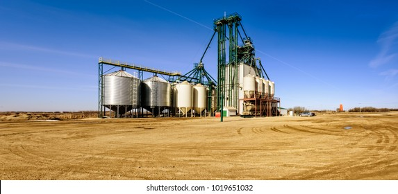 Agricultural industrial complex for cleaning and processing grain against the blue sky and yellow soil. Metal cisterns for grain, cars and truck.