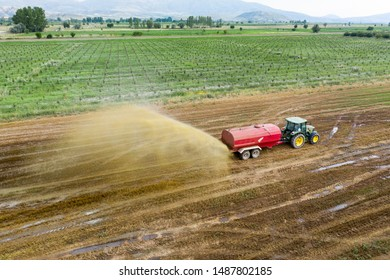 Agricultural land. Tractor with trailer fertilizing field with natural manure, throwing liquid manure to the field. Aerial drone view, from above.  Burdur -TURKEY 25.July.2019
