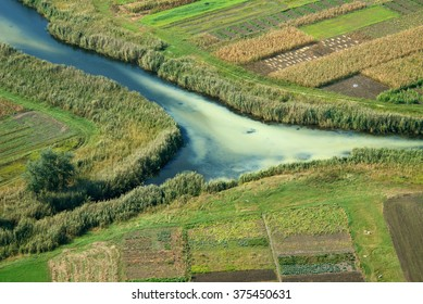 Agricultural lands near a little river, the view from a flying helicopter