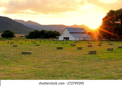 Agricultural landscape with a barn and hay bales in a field, Utah, USA.