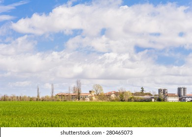 Agricultural landscape with farm and silos and a sky with clouds
