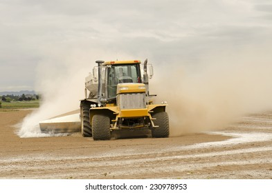 Agricultural lime being spread by a big tired truck or tractor  on a newly plowed farm field