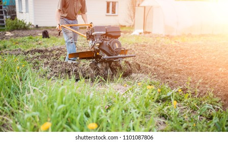 Agricultural machinery: cultivator for tillage in the garden. man Farmer plows the land with a cultivator, preparing it for planting vegetables, in a sunny garden
