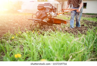 Agricultural machinery: cultivator for tillage in the garden. man Farmer plows the land with a cultivator, preparing it for planting vegetables, in a sunny garden.