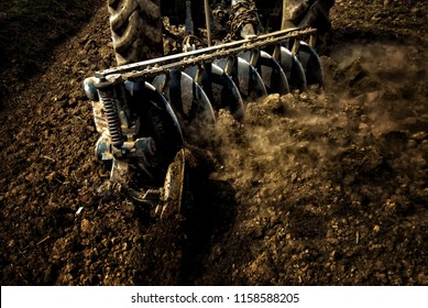 Agricultural machinery, tractor worker prepare soil for growing in the field.