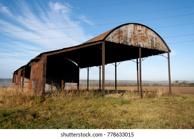 Agricultural metal barn in autumn with a blue sky and clouds
