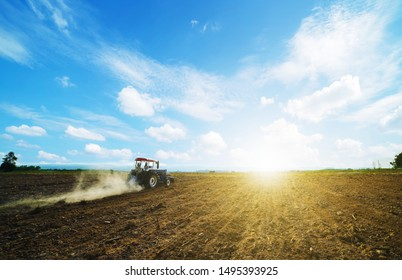 Agricultural people use a tractor as a tillage machine, which has a wide area to prepare the soil for growing corn on the farm.Beautiful sky clouds and sunlight background copy space.