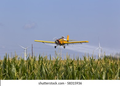 A agricultural plane dusts crops against a blue sky