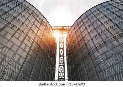 Agricultural Silos. Metal grain facility with silos. Storage and drying of grains, wheat, corn, soy, sunflower against the blue sky with white clouds