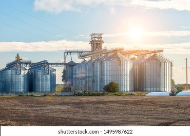 Agricultural Silos. Storage and drying of grains, wheat, corn, soy, sunflower against the blue sky with white clouds.Storage of the crop