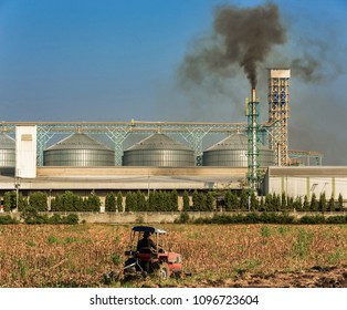 Agricultural silos with thick smoke from pipe emissions pollution into the atmosphere while a farm tracktor moving in the foreground.
