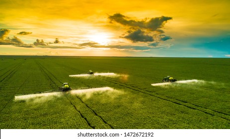 Agricultural sprayers making application at the end of the day with beautiful sunset - Shutterstock ID 1472672192