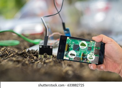 Agricultural technology concept. Smart farmer holding smart phone with agritech icons and messages on screen with soil sensor to manage water, soil quality and monitor weather.