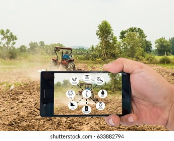 Agricultural technology concept. Smart farmer holding smart phone with agritech icons and messages on screen on farmer driving tractor background.
