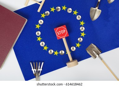 Agricultural tools,an indicator -access forbidden,pins,and a passport on an European flag.Background