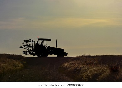 Agricultural tractor with farmers silhouettes go home in sunset