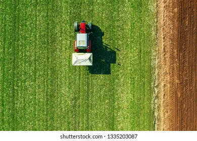 Agricultural tractor is fertilizing wheat crop field with NPK fertilizers, aerial view from drone pov