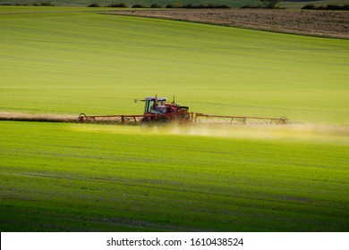 An agricultural tractor with outspread spraying arms  spreads green chemicals on a field in Hertfordshire, UK