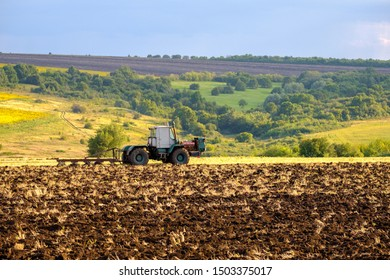 An agricultural tractor plows a field with a plow after harvesting wheat in the rays of the evening sun. Black fertile land.