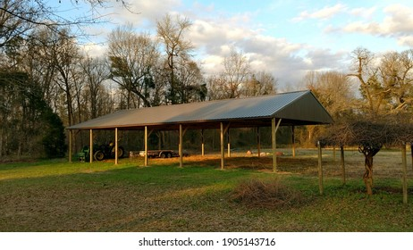 Agricultural tractor shed with green metal roof and green metal end walls with space for up to six pieces of farm equipment