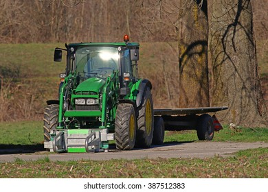 Agricultural tractor towing a flatbed trailer on rural farmland