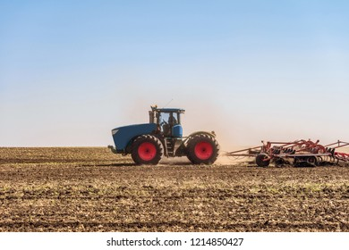 Agricultural tractor is working in the field under blue sky at daylight. Soil cultivation. Agrotechnical event that provides crumbling, loosening and partial mixing of the soil.