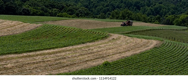 Agricultural web banner of a dairy farmer harvesting haylage on rolling hill fields in Appalachia