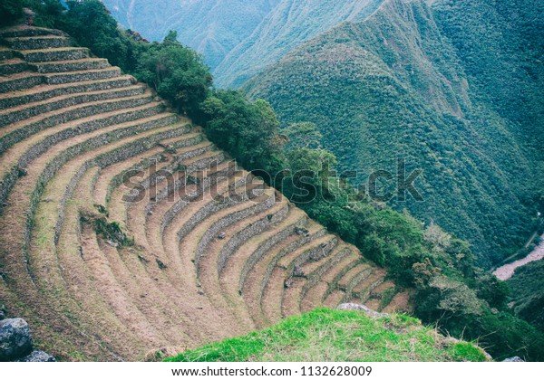 Agriculture centre terraces covered by grass with the Andes mountains on the background on the Inca Trail to Machu Picchu, Peru. Beautiful wallpaper.
