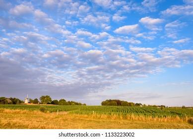 Agriculture countryside in Flemish Ardennes (Vlaamse Ardennen) village Tiegem. White wind mill (Tiegem Molen) on hill. Scenic landscape with beautiful clouds. Tiegem near Anzegem, Flanders, Belgium.