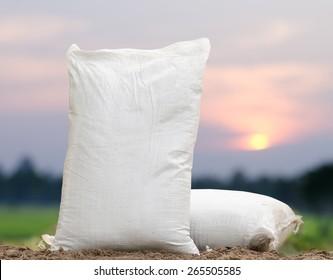 Agriculture farm with fertilizer bag over sunrise background