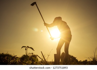 Agriculture life Concept : Black silhouette of a worker holding spade is digging soil at sunset light. Asian farmer holding spade and digging the soil.