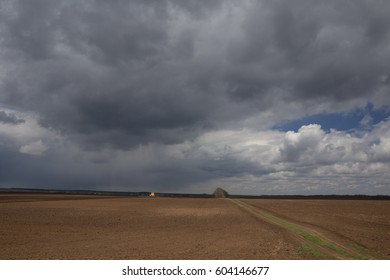 Agriculture.The tractor prepares the field for sowing wheat in early spring in the steppes of Kalmykia during a thunderstorm.