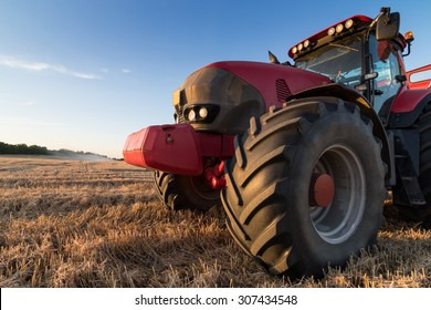 Agriculture tractor and tow trailer waiting to be filled at grain campaign at sunset on a stubble field