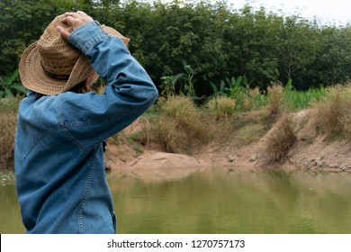 Agriculturist woman wore a hat with single hands holding the head. By the pool in the garden.