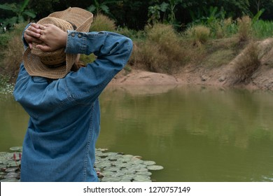 Agriculturist  woman wore a hat with two hands holding the head. By the pool in the garden.