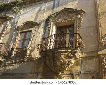 Agrigento is a city in Sicily, in the south of Italy. Agrigento is a rich ancient city. The baroque building of the photo has a classic facade. The window has a nice terrace.