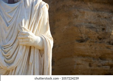 Agrigento / Italy - 08/14/2016: Detail of a hand holding a tunic of a white marble statue present in the ruins of the Temples of Agrigento