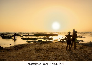 AGRIGENTO, SICILY, ITALY - AUGUST 25, 2008: father and sons enjoy the view of the sunset on the sea of Sicily in summer vacation