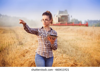 agronomist girl in glasses with hair tied in a ponytail with tablet controls the harvesting in wheat field. Image released.