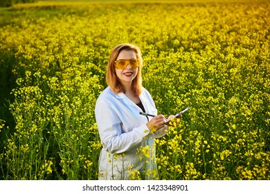 Agronomist woman or farmer examine blossoming rape (canola) field using tablet