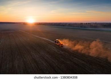 Agronomy. Tractor plowing field at sunset. Soil cultivation. Spring agricultural work in field. Rural landscape.