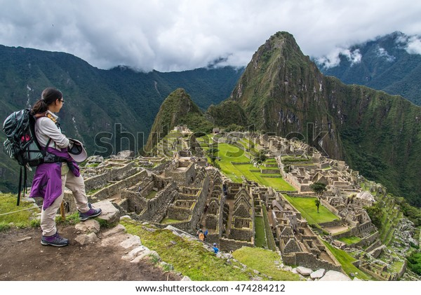 AGUA CALIENTES, PERU JAN 2, 2013 : A female traveller with backpack standing in front of Machu Picchu after finished Inca trail