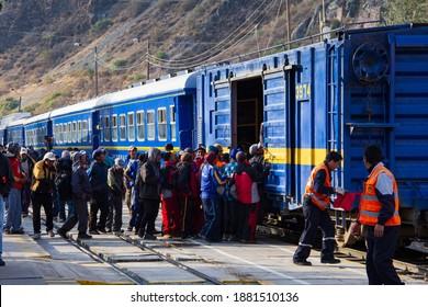 Aguas Calientes, Peru - June 24, 2015:  Workers load onto a freight car on a Peru Rail train at the Aguas Calientes stop near Macho Picchu.
