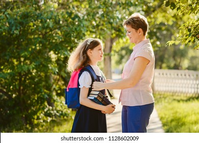ahappy mother accompanies her daughter to school