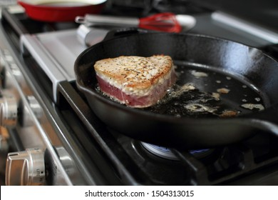 Ahi tuna steak searing in a cast iron skillet on a gas stove.